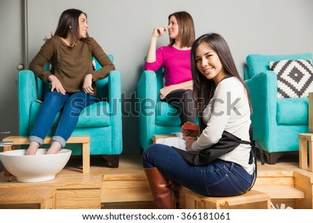 Portrait of a gorgeous Hispanic young woman working at a nail spa and giving a pedicure to a couple of women - stock photo