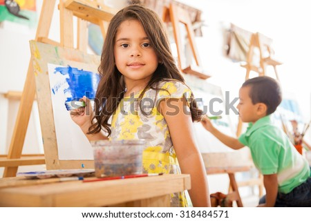 Portrait of a gorgeous little Hispanic girl holding a paintbrush and working on a painting for art class - stock photo