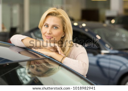 Portrait of a gorgeous mature blond haired woman leaning on her new automobile posing at the car dealership copyspace buying happiness enjoyment lifestyle rental leasing driving ownership.
