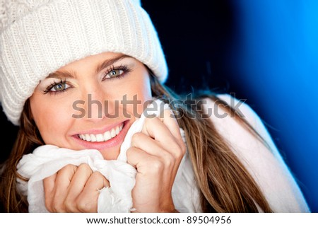 Portrait of a gorgeous winter woman smiling - over a blue background - stock photo