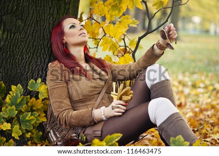 Portrait of a gorgeous woman reading a book in the autumn park. - stock photo
