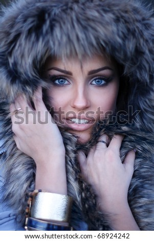 portrait of a gorgeous woman with a furry hood on her head - stock photo