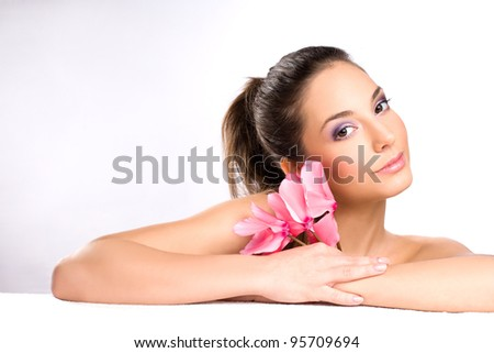 Portrait of a gorgeous young brunette spa girl with pink flowers.