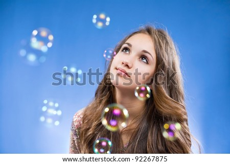 Portrait of a gorgeous young brunette teen admiring the soap bubbles. - stock photo