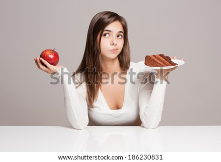 Portrait of a gorgeous young brunette woman and food choices. - stock photo