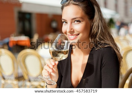 Portrait of a gorgeous young brunette woman having wine fun. - stock photo