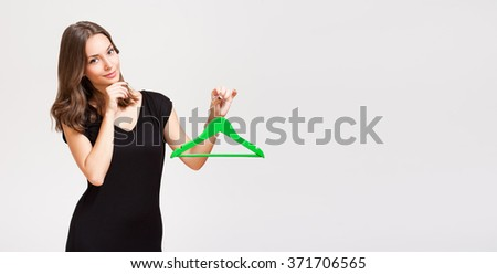Portrait of a gorgeous young brunette woman holding clothes hanger. - stock photo
