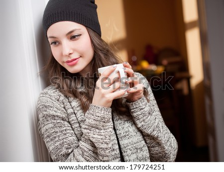 Portrait of a gorgeous young brunette woman relaxing with mug of hot beverage.