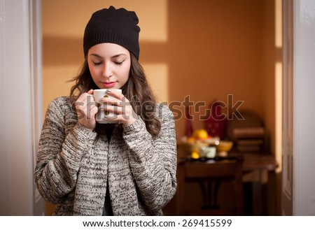 Portrait of a gorgeous young brunette woman relaxing with mug of hot beverage. - stock photo