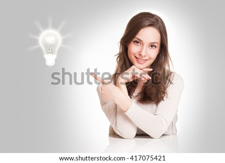 Portrait of a gorgeous young brunette woman with light bulb idea symbol.