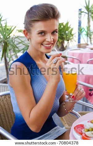 Portrait of a gorgeous young female drinking orange juice at cafeteria - Outdoor