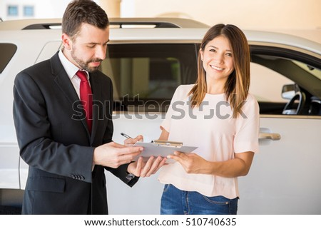 Portrait of a gorgeous young Hispanic woman signing a finance contract for a new car at a dealership and smiling