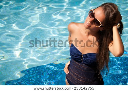 Portrait of a gorgeous young woman enjoying a day in the pool. Relaxing in crystal blue water. - stock photo
