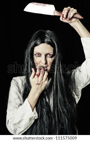 Portrait of a gory and scary zombie with red eyes on black background holding knife - stock photo