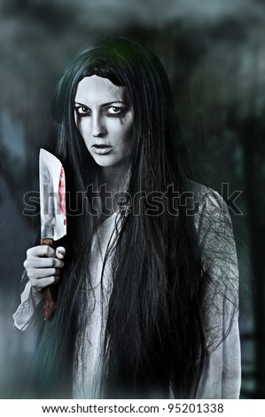 Portrait of a gory and scary zombie woman on black background holding knife - stock photo
