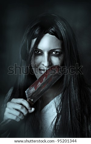 Portrait of a gory and scary zombie woman on black background licking bloody knife