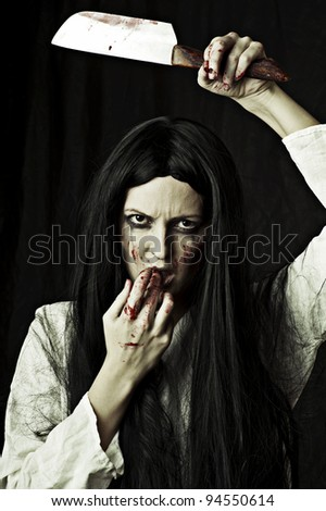 Portrait of a gory bloody and scary zombie woman on black background holding knife - stock photo