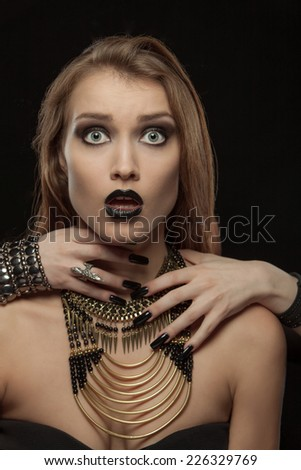 Portrait of a gothic woman with hands of vampire on her neck on black background. Halloween - stock photo