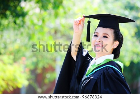 Portrait of a graduation student looking up outdoors - stock photo