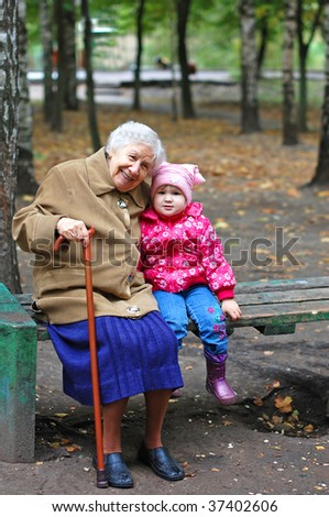 portrait of a grandmother and granddaughter in the park - stock photo