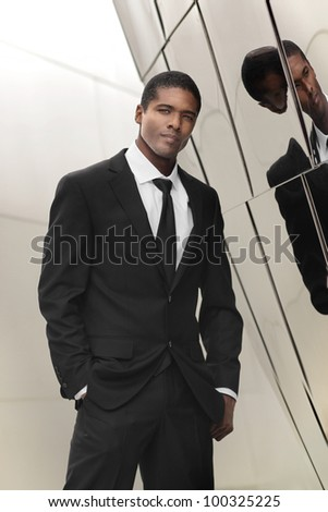 Portrait of a great looking young ethnic businessman in elegant black and white suit against shiny reflective wall - stock photo