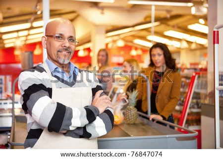 Portrait of a grocery store cashier standing at a checkout counter - stock photo