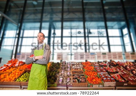 Portrait of a grocery store clkerk or owner in front of a vegetable counter - stock photo