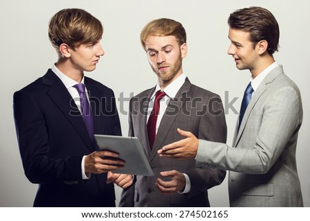 portrait of a group of businessman discussing about their ideas isolated on grey - stock photo