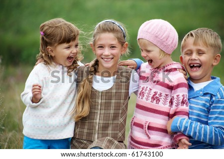 portrait of a group of children happily laughing and playing on the grass - stock photo