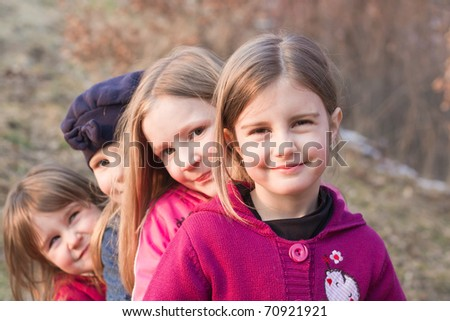 portrait of a group of children happily laughing and playing outside - stock photo