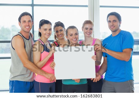 Portrait of a group of fitness class holding blank paper at a bright exercise room - stock photo