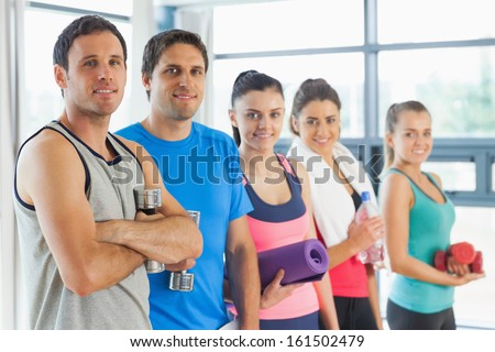 Portrait of a group of fitness class standing in row at a bright exercise room