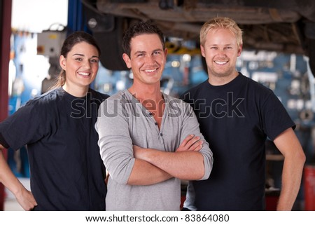 Portrait of a group of mechanics standing in a shop - stock photo
