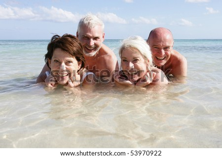 Portrait of a group of smiling seniors bathing in the sea - stock photo