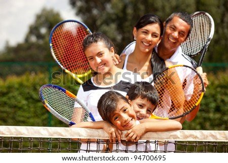 Portrait of a group of tennis players smiling outdoors - stock photo