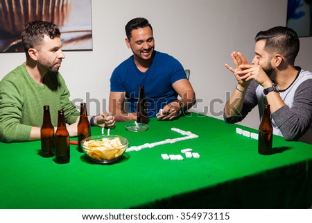 Portrait of a group of three men drinking some beer, laughing together and playing dominoes at home - stock photo