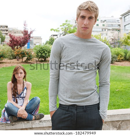 Portrait of a group of two fashionable and attractive teenagers friends relaxing together while visiting a park in a city during a summer day out. Teenagers outdoors lifestyle. - stock photo