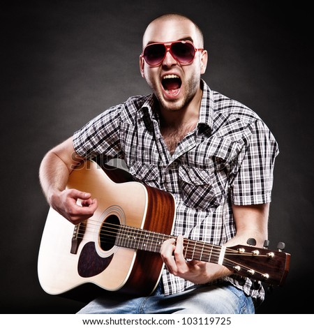 Portrait of a guitarist on a black background. a man shouts out loud and fun - stock photo