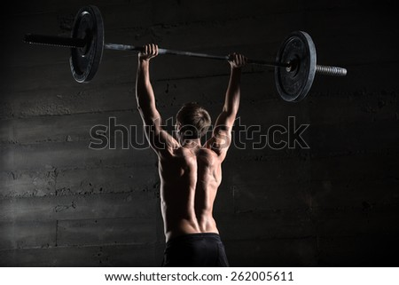Portrait of a handsome athlete from behind. Athlete raises the barbell over your head. Studio shots in the dark tone. - stock photo