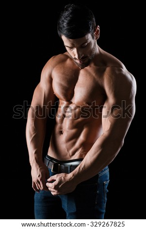 Portrait of a handsome athletic man posing on black background