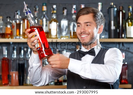 Portrait of a handsome bartender standing at the counter smiling and holding a bottle of liquor, shelves full of bottles with alcohol on the background - stock photo