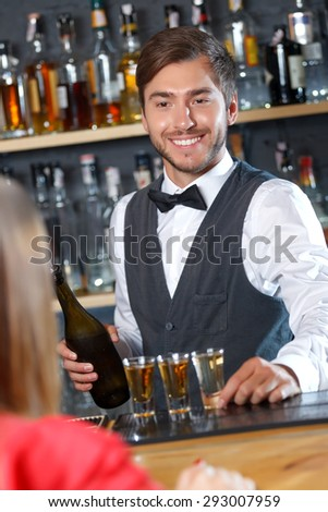 Portrait of a handsome bartender standing at the counter smiling and holding a shot glass looking at a woman sitting back to us, shelves full of bottles with alcohol on the background