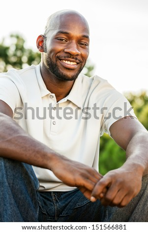 Portrait of a handsome black man in his late 20s sitting at the park outdoors in summer