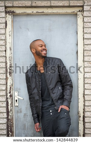 Portrait of a handsome black man laughing outdoors - stock photo