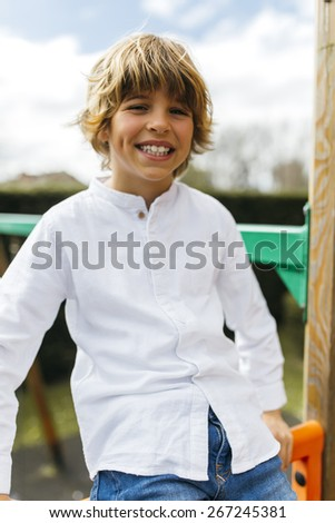 Portrait of a handsome blond little boy in the park - stock photo