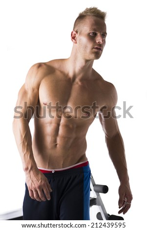 Portrait of a handsome blond muscular young man next to gym bench, isolated over a white background - stock photo