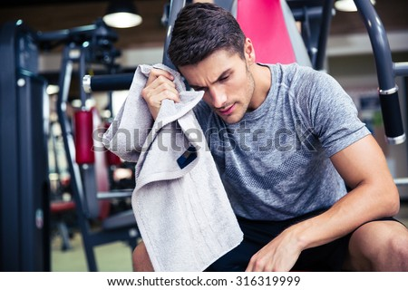 Portrait of a handsome bodybuilder wipes the sweat at fitness gym - stock photo