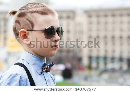Portrait of a handsome boy with a creative hairstyle on background of the city. A boy with a fashionable hairstyle in blue shirt. Boy in sun goggles. Sunglasses have a little boy. - stock photo