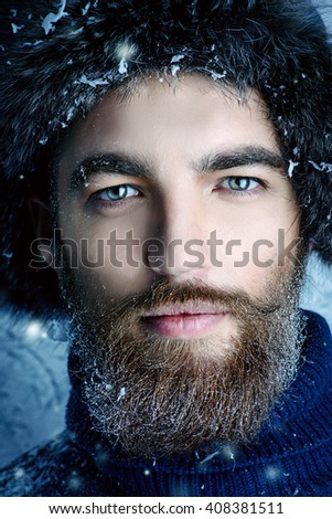 Portrait of a handsome brutal man with beard and mustache dressed in winter clothes, covered with snow. - stock photo