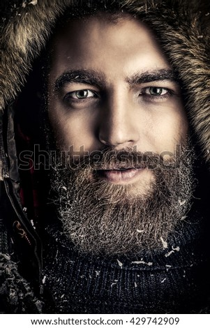 Portrait of a handsome brutal man with beard and mustache dressed in winter clothes, covered with frost. - stock photo